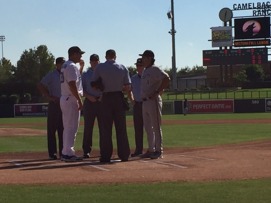 Saguaros Manager Carlos Subero exchanges lineups with Desert Dogs skipper Bill Haselman.